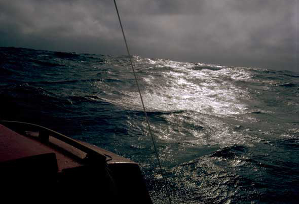 The cabin of a boat with a choppy sea and moody grey sky behind it