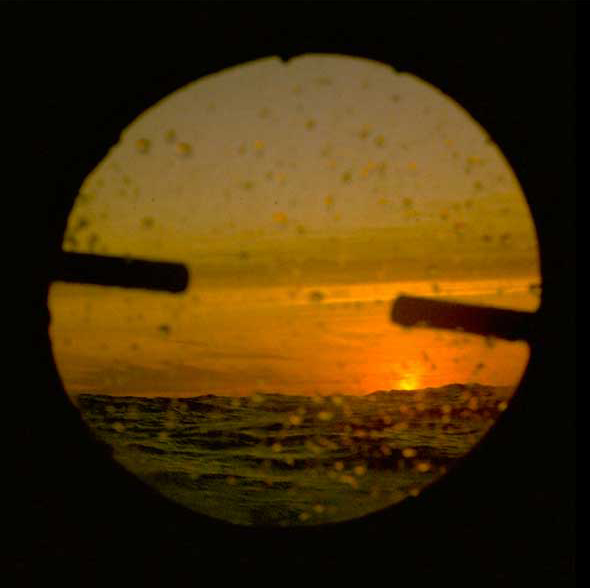 An orange sunset out at sea, viewed through a porthole