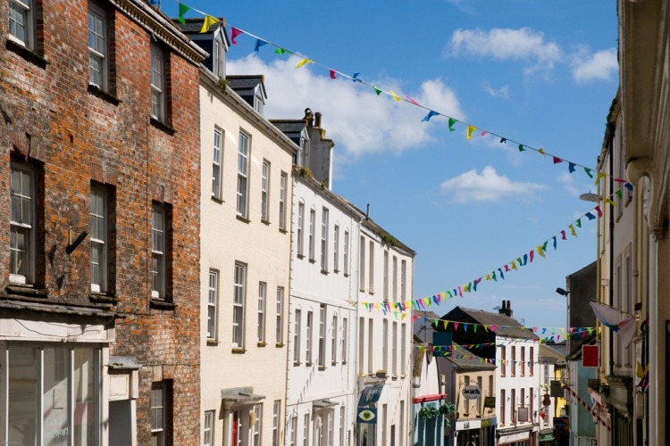 Looking down a Falmouth street with tall buildings on either side, with colourful bunting through the centre.