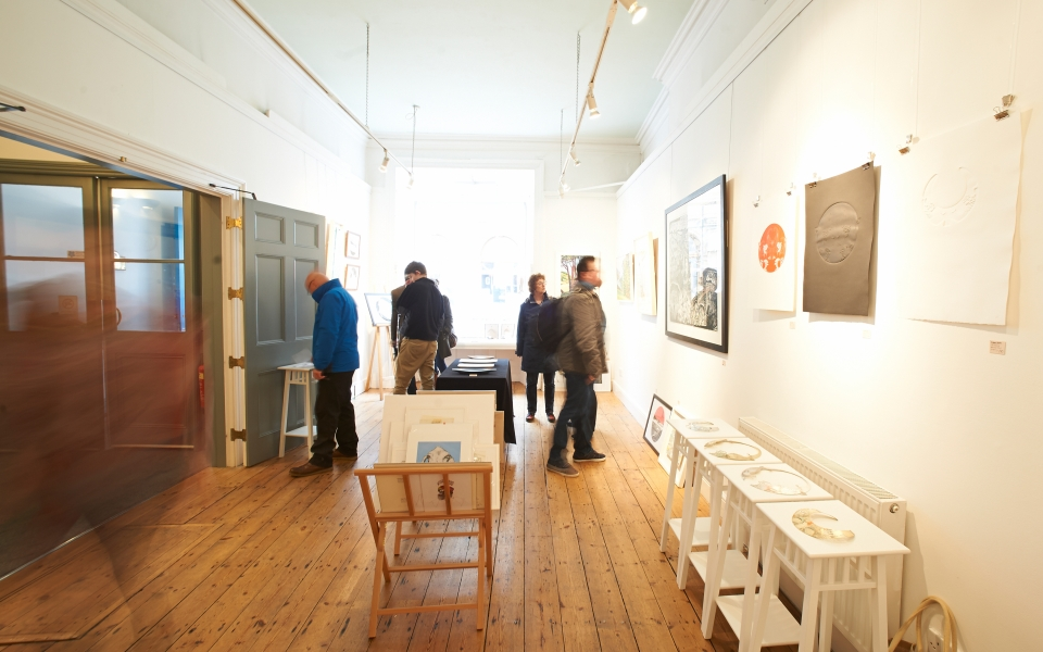 An interior shot of a light, wooden floored gallery, with a few people looking at artworks on the walls.